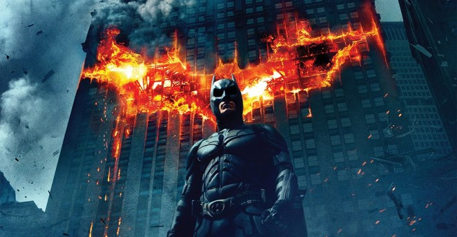 Batman stands in front of a building which has a flaming bat upon it