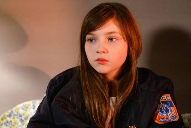 Piper sitting on a bed wearing Jo's jacket