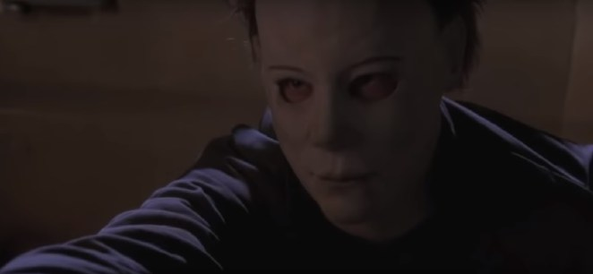 Micheal Myers reaching out his hand with a devious look on his face
