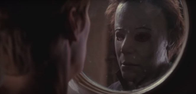 Laurie Strode comes face to face with her brother, masked killer Micheal Myers, as they stare at each other through a circular glass hole in a door