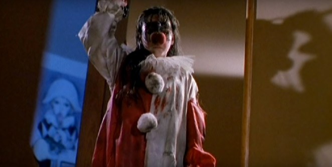 Jamie, in her clown costume and mask, covered in blood and brandishing scissors.