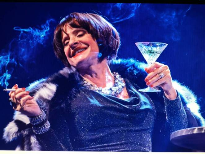 Patti Lupone as Joanne, holding a martini glass and a cigarette, looking languidly happy about something.