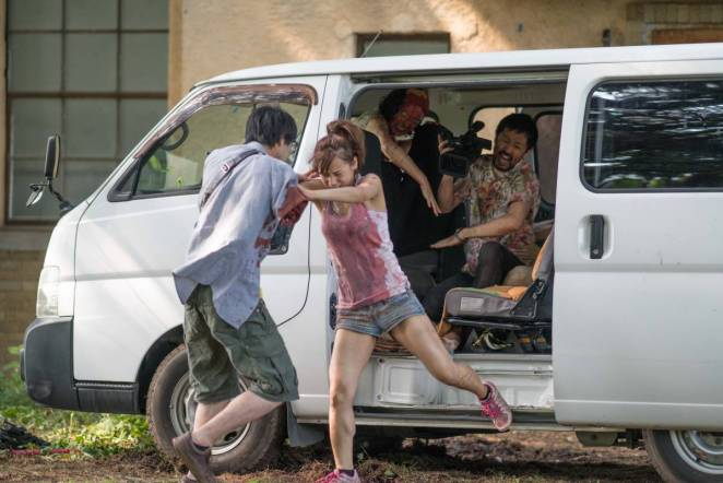 Aika pushes a zombie out of the van as the cast and crew hide away.