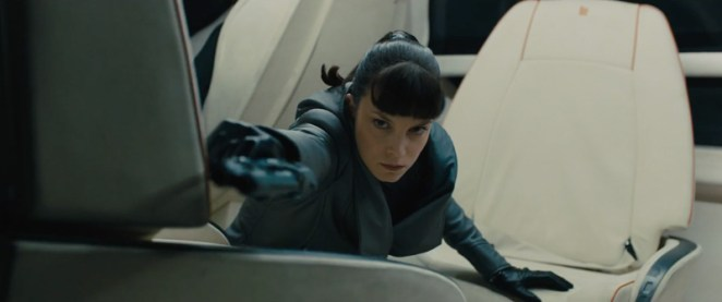Luv takes aim with her gun at officer K , while she tries to find the replicant child