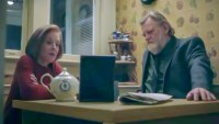 Ira and Bill sit having tea in her kitchen at the dining room table, looking at a photo frame