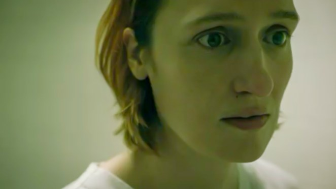 Lou in her psychiatric hospital scrubs, staring worringly, afraid to turn around.