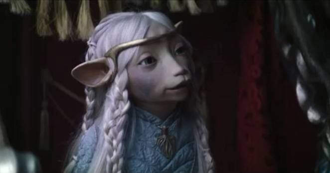 Princess Brea, a Gelfling, seated in a luxurious carriage.