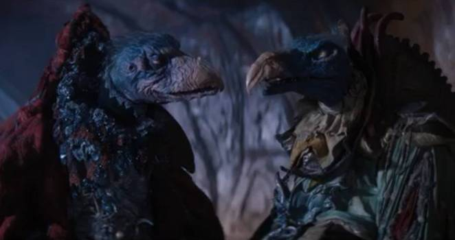 Two Skeksis, The Chamberlain and The Scientist, look at each other in the catacombs.