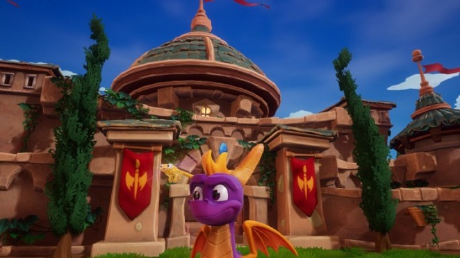 Spyro stands in front of a structure with red flags on each side of Spyro.
