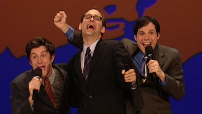 The three suit-wearing men of Stella cheer during their live comedy act.