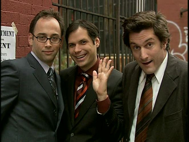The three suit-wearing men of the TV series Stella acknowledge the audience.