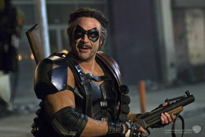 Image from 2009 Watchmen film of Comedian in armored costume smiling and holding a riot gun.