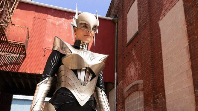 Miss Lint in her Joan of Arc costume, standing in a brick alley.
