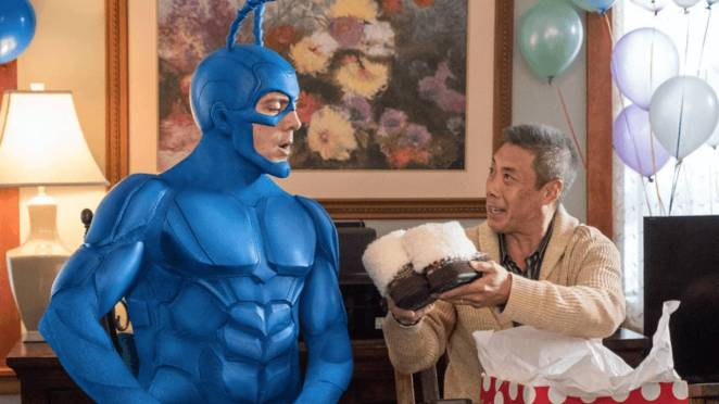 Walter shows the Tick a pair of shoes, open birthday present box on his lap, party balloons in the background.