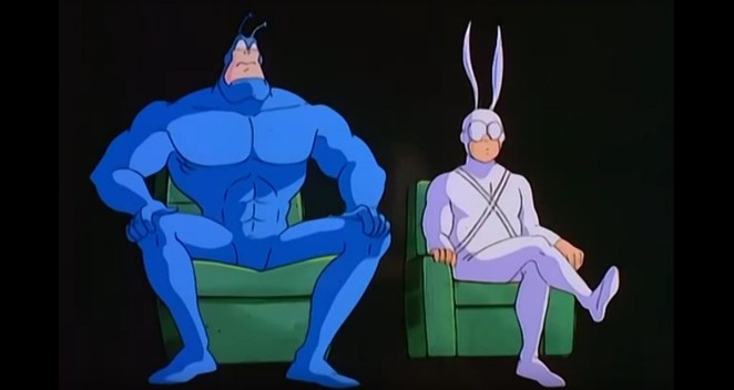 The Tick and Arthur, sitting on green chairs in an interrview about the Tick's life, from the first episode of the 1994 cartoon on FOX Kids.