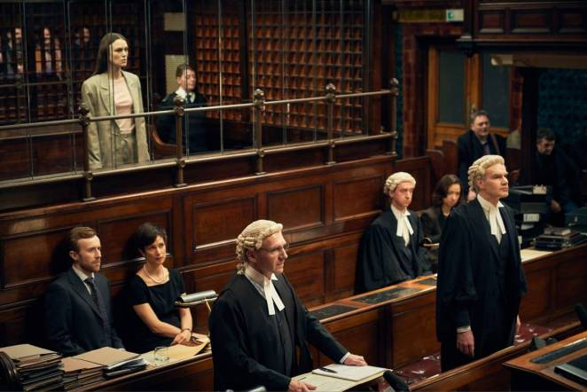 Katharine Gun (Kiera Knightley) stands in a court room awaiting the judge's verdict with her lawyer Ben Emmerson (Ralph Fiennes) and several other solicitors wearing judicial wigs