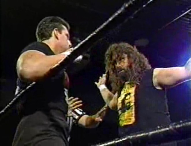 Cactus Jack has Tommy Dreamer backed against the ropes in the ring, while a referee attempts to intervene
