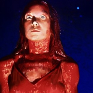 Carrie covered from head to toe in blood stares ahead with horror