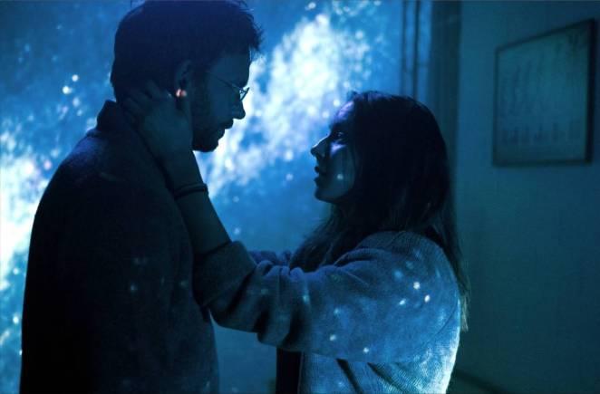 Clara (Bellisario) comforts Isaac (Adams) in front of their projector map.