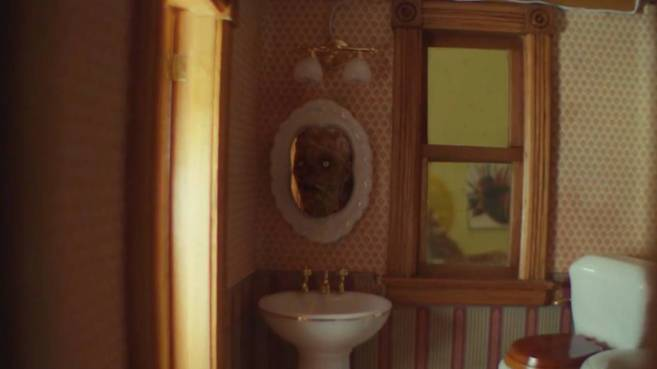 "Image of the severed corpse doll head in the dollhouse bathroom mirror in Creepshow's ""The House of the Head"""