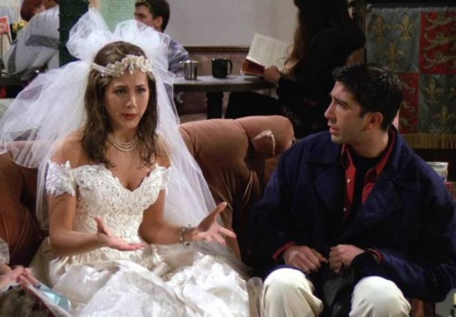 Rachel is in her wedding dress explaining why she ran out on her own wedding while on the same couch in the Central Perk, Ross looks on gobsmacked.