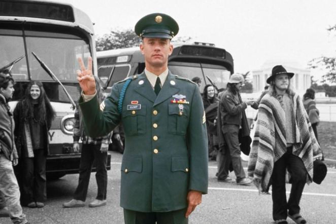 Forrest in military uniform making a peace sign with hippies in the background