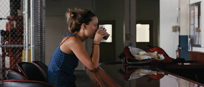 Kate (Olivia Wilde) takes a sip of a beer in her workplace lounge.