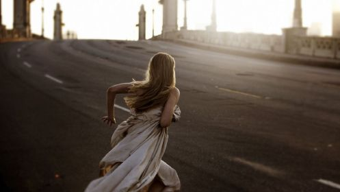 Maggie runs covered only in a sheet across a bridge in The Sound of my Voice