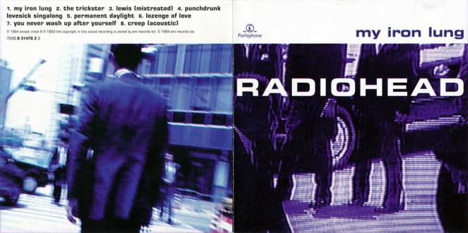the back and front of Radiohead's My Iron Lung CD packaging focuses on a purple colored abstract candid shot of a street scene with people's legs on the front, and a blue filtered street scene of the back of a man on the back.