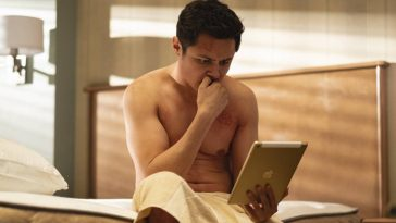 Craig (Arturo Castro) sits on the bed of Room 104 in a towel looking intently at his iPad