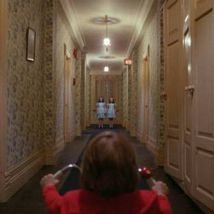 Danny rides up to twin girls in a corridor