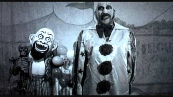 Captain Spaulding stands next to a puppet in his gas station commercial