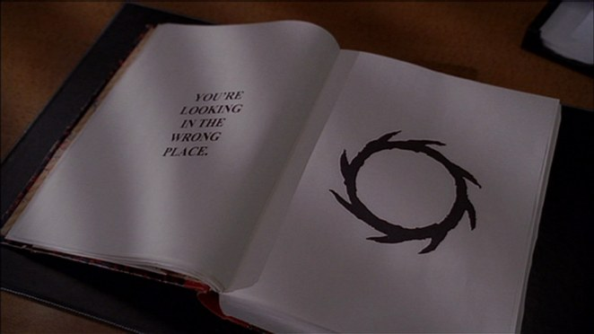 "An open book, with an illustration of a thorny circle on one page, and ""you're looking in the wrong place"" written opposite it."