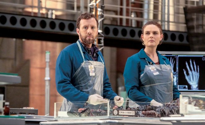 Hodgins and Brennan, wearing plastic aprons and working in the lab