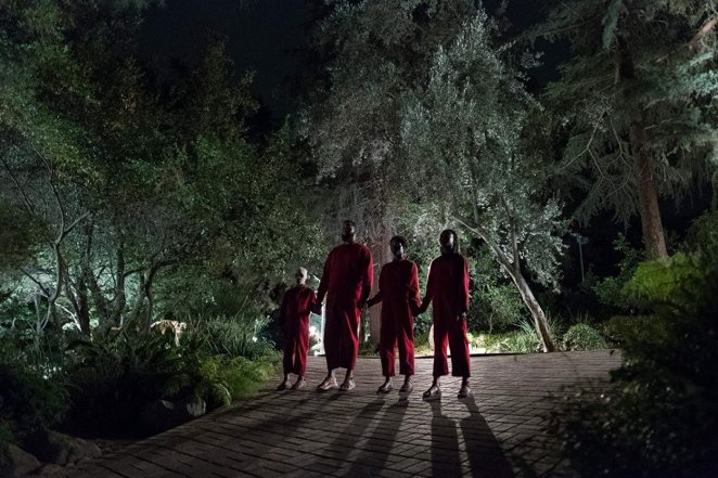 A Family of a boy, father, mother, and daughter, stand in the dark wearing red coveralls
