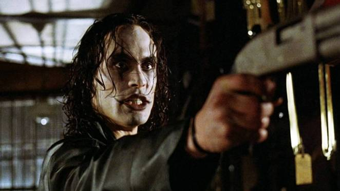 Eric Draven (Brandon Lee) aims a gun at someone off-camera