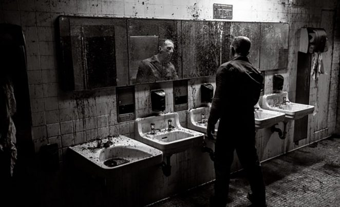 A shot of a filthy bathroom while a deformed janitor attempts to clean it.