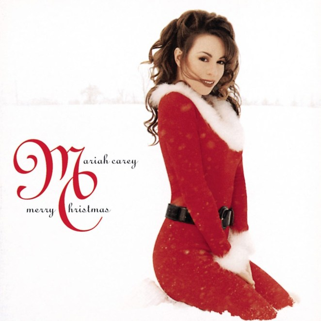 Mariah Carey is in a red Santa suit (no hat), coyly sitting outside in an otherwise white snowy scene.