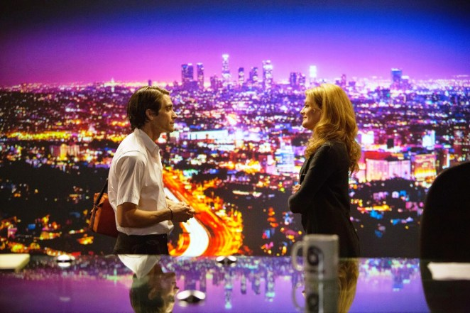 Lou Bloom talks to Nina in front of a display of LA lit up at night on the news desk