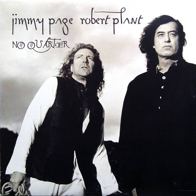 In black and white, we see Robert Plant on the left wearing a black coat with white sleeves, and Jimmy Page stands next to him, all in black.