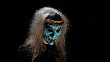 One of the film's antagonists, a woman wearing a blue witch mask, stands surrounded by darkness