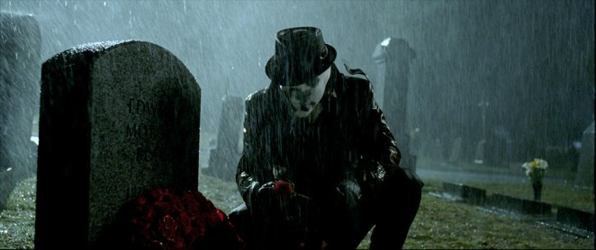 Rorschach kneels in front of a gravestone