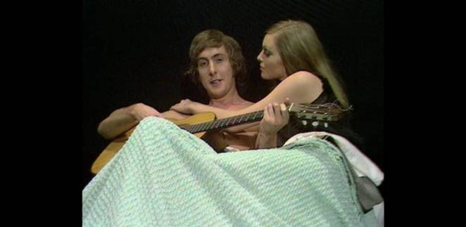 Eric Idle lies in bed playing guitar while being caressed by a beautiful woman
