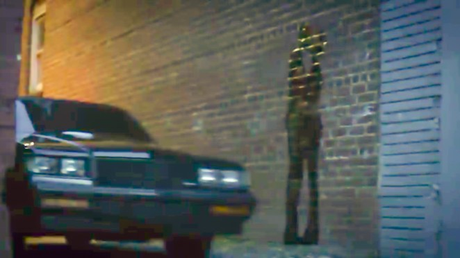 Watchmen S1E2 - A car drives by a brick wall with a graffiti silhouette of a couple kissing.