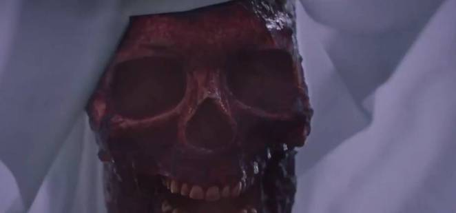 Close up shot of a bloody skull beneath a sheet.