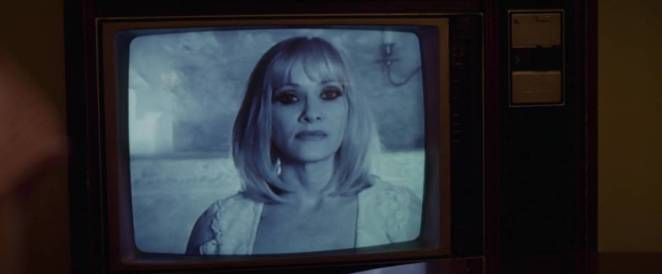 Barbara Crampton appears on a black-and-white TV set in Beyond the Gates