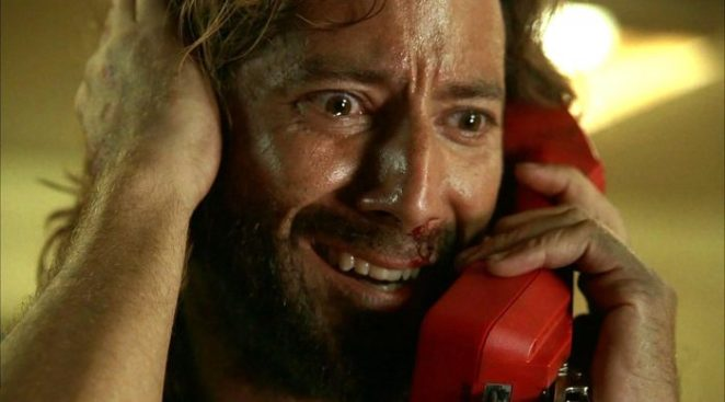 "Desmond holds the telephone to his ear as he calls Penny in Lost's ""The Constant"""