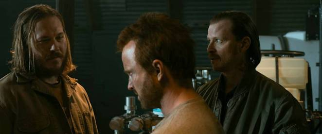 Neil and Kenny stand on either side of Jesse as they make a bet over whether he can break the rig in the meth lab