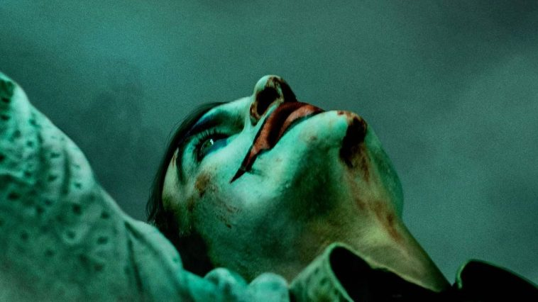 Joaquin Phoenix is the titular Joker with clown face looking up at the sky