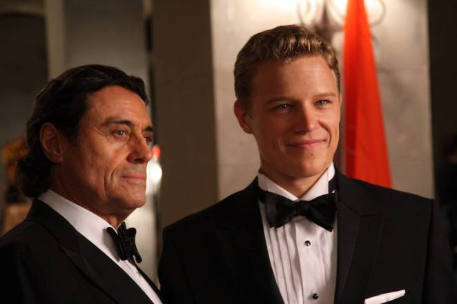 King Silas and David, both wearing black tie, are looking at something offscreen. David is smiling.